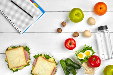 Top view planning notebook with copy space and healthy breakfast. Sandwich with ham and cheese, eggs, cucumber, tomato and bottle of water on white wooden table.