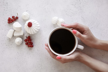 Women's hands holding a Cup of coffee on a white background. Marshmallows, red berries.