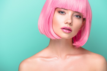 attractive young woman with pink bob cut and stylish makeup looking at camera isolated on turquoise