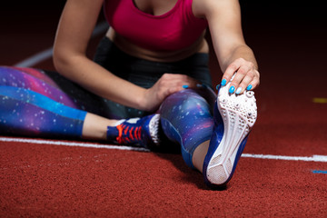 young athletic woman doing exercises on flexibility. stretching legs sitting track stadium, night with reflectors