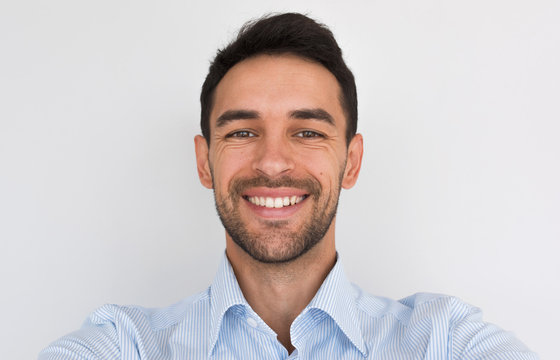 Closeup portrait of happy handsome young male smiling with healhty toothy smile looking at the camera, making self portrait. Cheerful unshaven man wearing blue shirt posing in studio background.People