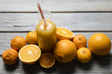 Fresh orange juice in a bottle with oranges on a rustic wooden background