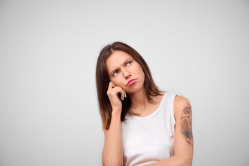 Horizontal portrait of attractive brunette female has unhappy look, thinks how to solve her problem, looks up, poses against white background with copy space
