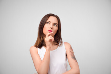Beautiful brunette female with puzzled expression, keeps finger on lips, looks aside with bewilderment, poses against gray background. Body language and face expression