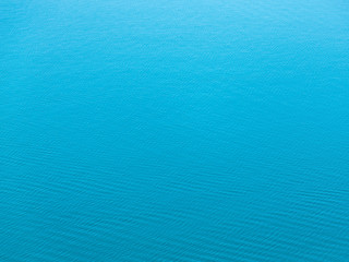 Sea texture of the water surface with slight ripples in sunny day. Bird's eye view.