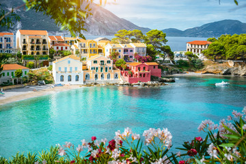 Turquoise colored bay in Mediterranean sea with beautiful colorful houses in Assos village in Kefalonia, Greece
