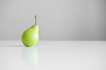 One green yellow pear with a twig stands on a white table, a reflection, a bright light, minimalism and free space for text.