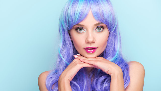 attractive young woman with blue hair looking at camera isolated on blue