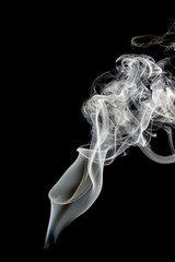 Abstract beautiful art. White smoke from the incense isolated on a black background.
