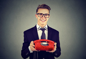 Cheerful businessman with red phone