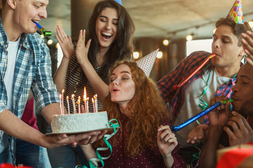 Friends presenting birthday cake to girl