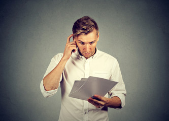 Concerned man reading paper documents