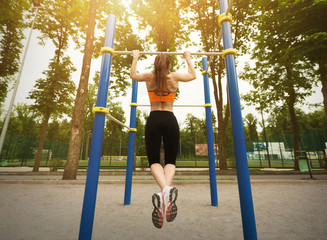 Girl doing workout on sports ground in park