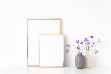 Gold portrait a4 and a5 frame mockup with wild lilac bellflower in vases near wall on white background. Empty frame mock up for presentation design. Template framing for modern art.