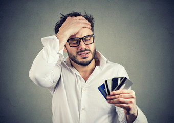 Stressed man having debts with credit card