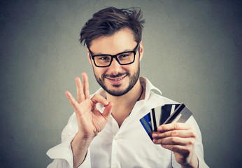 Smiling man showing OK gesture and credit cards