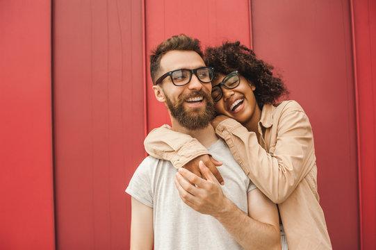 happy young multiethnic couple in eyeglasses hugging on street