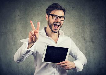 Hipster man showing tablet and v sign