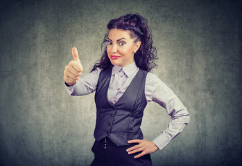 Young business woman showing thumbs up gesture
