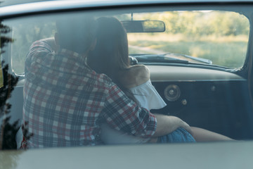 couple, man and woman are sitting in the car, the guy is hugging the girl. traveling together