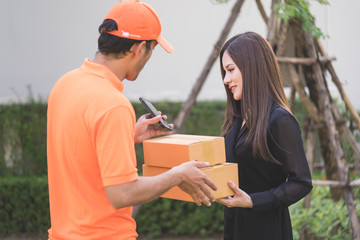 Delivery man is asking woman to sign mobile for the delivery.