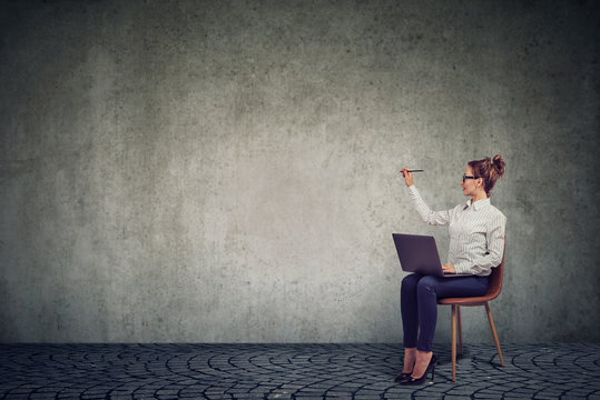 Young woman sitting on a chair with laptop writing on the wall