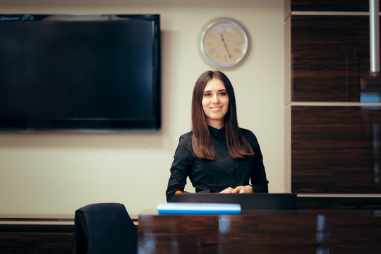 Receptionist Woman in front of Her Desk Greeting Customers