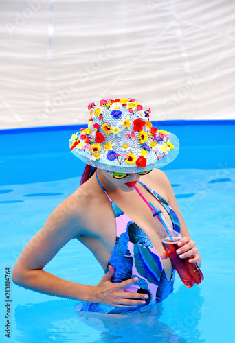 A young woman wearing a multi colored bathing suit also has ...