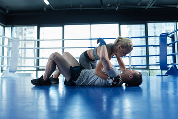 With boyfriend. Appealing blonde-haired female fighter really enjoying training with her boyfriend