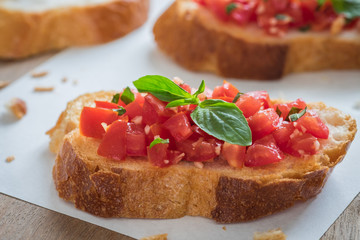 Bruschetta bread with chopped tomato and basil on paper
