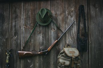 Foto auf Gartenposter Jagd Professional hunters equipment for hunting. Rifle, hat, bag and others on a wooden black background.