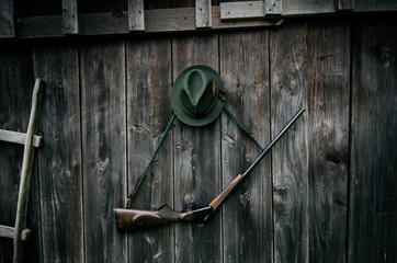 Zelfklevend Fotobehang Jacht Professional hunters equipment for hunting. Rifle, hat, bag and others on a wooden black background.