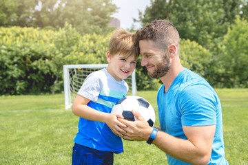 Man with child playing football outside on field