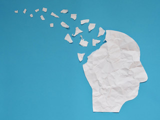 Wall Mural - Brain disorder symbol presented by human head made form crumpled paper torn on blue background with copy space. Creative idea for Alzheimer's disease, dementia, memory loss and mental health concept.