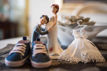 Composizione con statuine sposi, scarpette da neonato e mini vestito