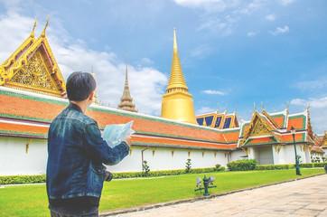 Young man traveler looking the Map in Wat Phra kaew at Bangkok Thailand. Traveling in Bangkok Thailand