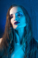 Art style portrait in blue tones of a lonely beautiful sad model girl behind a window glass, over which rain drops down