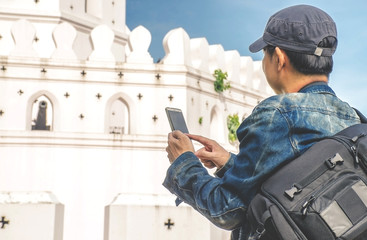 """man traveler with bag cross body and hat and look a map at """"Phra Sumen Fort"""" background from Bangkok Thailand. Traveling Thailand."""