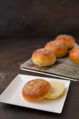 Homemade Hamburger Buns Topped with Sesame Seeds on a Rustic Black Background; One Cut Open on White Square Paper Plate
