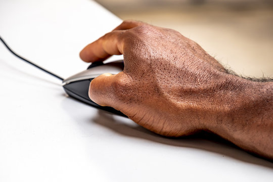 African man using mouse to control the computer