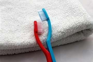Blue and red toothbrushes in hug laying on white towel, romantic valentines day concept or couple in love in welness hotel honeymoon relaxing.