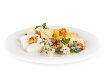 Cheese plate: Parmesan, cheddar, gouda, mozzarella and other with walnuts, cranberries and mint on a plate. Isolated