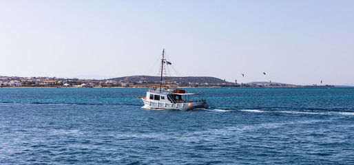 Greece. Aegean sea, Cyclades. Boat travelling, kite surfers and blue sky and sea background
