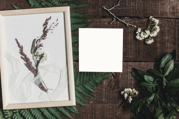wedding invitation mock-up and rustic boutonniere under glass frame on wooden  background with fern leaves. rustic barn wedding concept. top view. flat lay, empty card