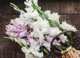 beautiful pink and white gladioluses in stylish wicker basket on rustic wooden background flat lay. colorful gladioli on rustic wood, space for text, greeting card. spring image. instagram
