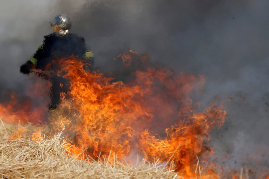 A French fireman uses a shovel behind flames in a burning field of barley during harvest season in Niergnies