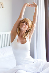 Pretty young woman stretching after wake up in the bedroom.