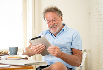 Handsome senior retired old man using tablet with joy while having breakfast at home