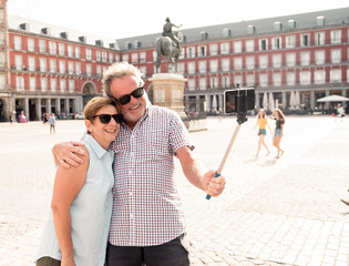 Happy retired senior tourist Couple Standing Taking Selfie in a European city