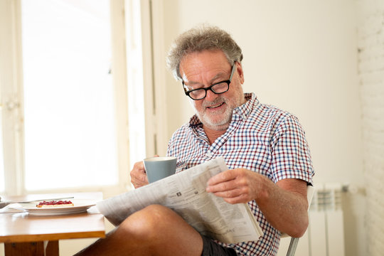 happy old man reading the newspaper while having breakfast